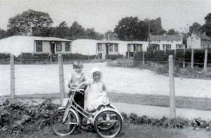 This picture shows the prefabs in what is now Greenvale Drive with St John's Road running off to the right. The children are Brian and Jennifer Robinson in 1955